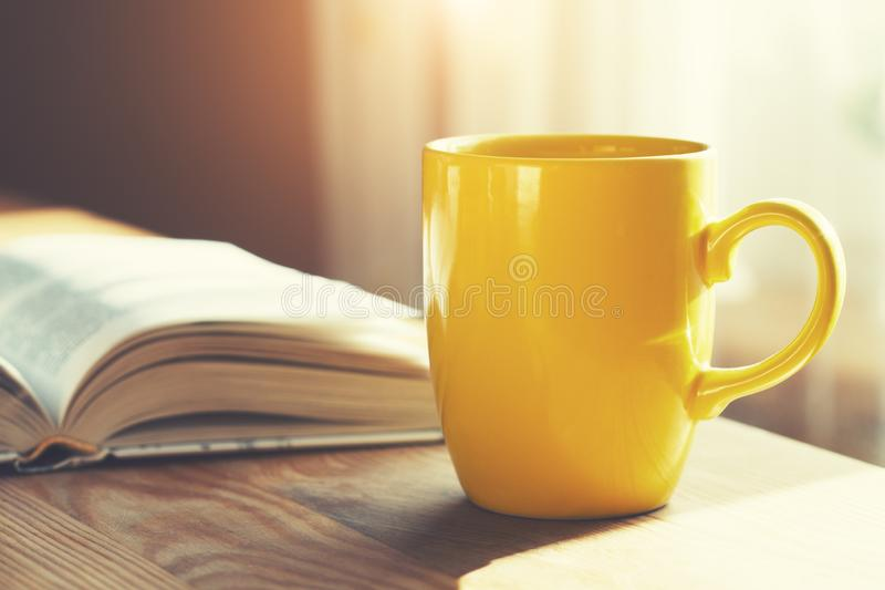Tasse de café et livre ouvert sur la table en bois, fond de lumière du soleil de matin photographie stock
