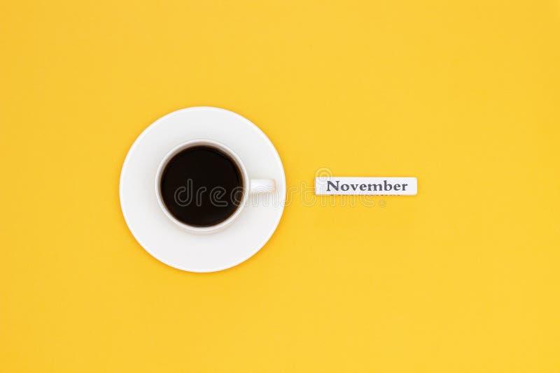 Tasse de café et de texte NOVEMBRE sur le fond jaune photo stock