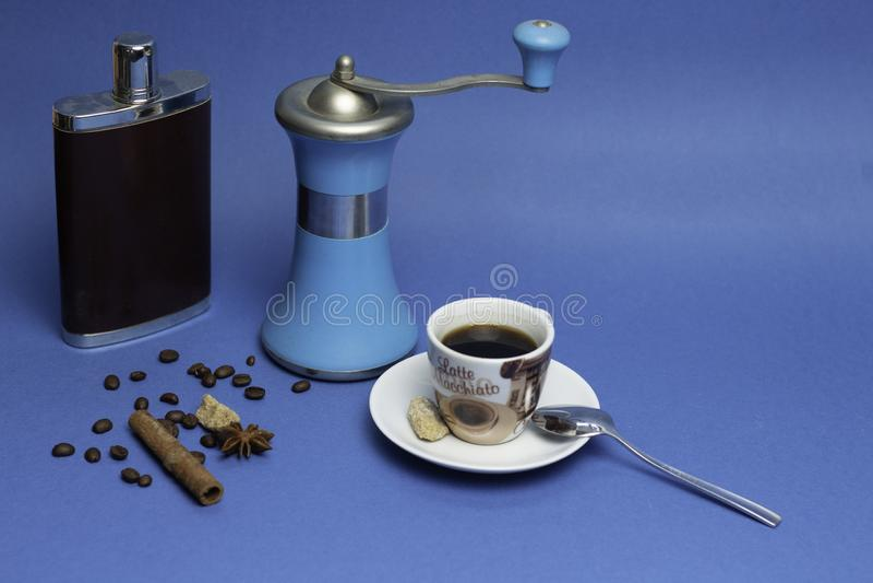 Tasse de café, de flacon avec le cognac et de broyeur de café de manuel sur un fond bleu image stock
