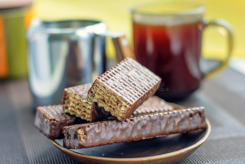 Tasse de café, gaufres de chocolat et une cruche de lait photographie stock libre de droits