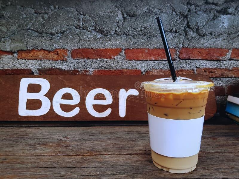 Tasse de café glacée de Latte sur le Tableau en bois devant le label de bière contre le mur de briques image libre de droits