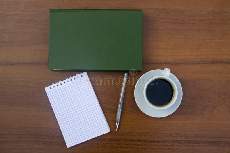 Tasse de café, de livre, de bloc-notes et de stylo sur le bureau en bois photos stock