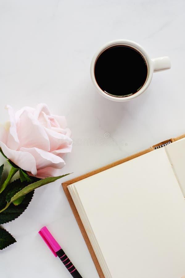 Tasse de café noir avec le carnet ouvert, le stylo et la rose douce de rose photos libres de droits