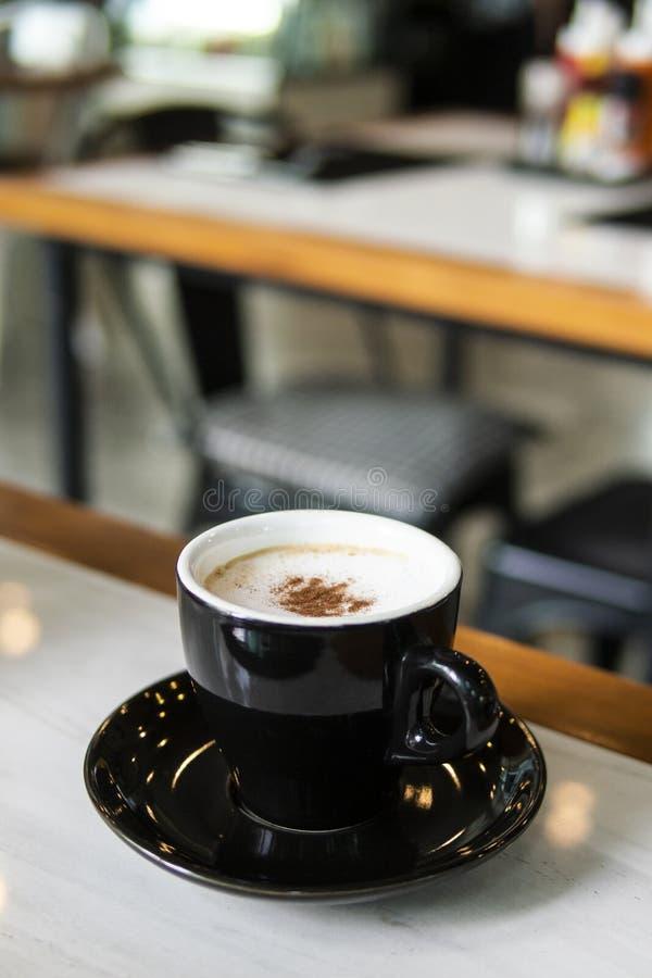 Tasse de café noir et café chaud de cappuccino sur la table en bois blanche Fond de tache floue photo libre de droits