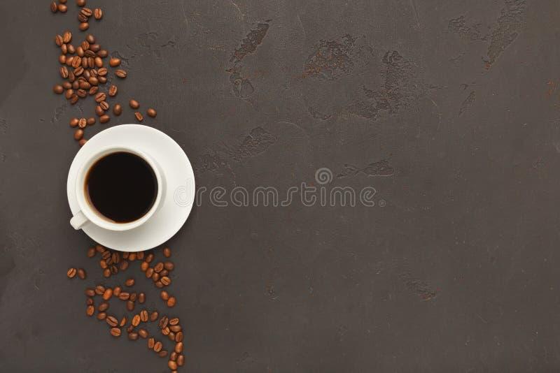 Tasse de café noir et de haricots dispersés sur le fond gris photo stock