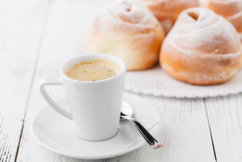 Tasse de café noir et de petit pain doux pour le petit déjeuner, plan rapproché photos stock
