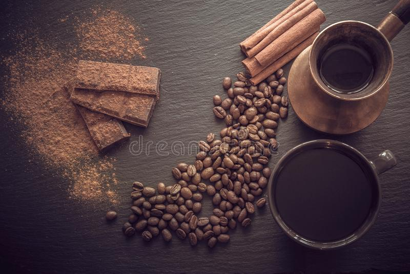 Tasse de café noir, de grains de café, de barre de chocolat, de cannelle et de vieux cezve sur l'ardoise noire comme fond avec l' photographie stock libre de droits
