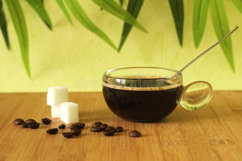 tasse de café noir sur un plancher en bois en bambou brun avec des morceaux de sucre empilés à côté de lui et des grains de café  photographie stock libre de droits