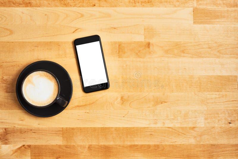 Tasse de café noire avec le smartphone noir sur la table en bois photos libres de droits