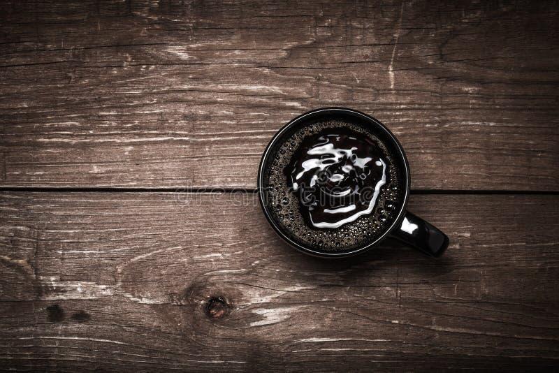 Tasse de café noire sur la vieille table en bois toned photo stock