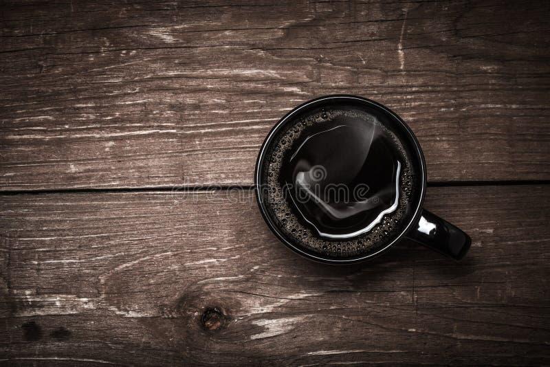 Tasse de café noire sur la vieille table en bois toned photographie stock libre de droits