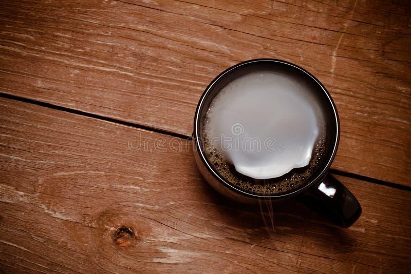 Tasse de café noire sur la vieille table en bois toned photos stock