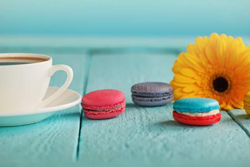 Tasse de café ou de thé avec la fleur et les macarons jaunes sur le fond bleu photographie stock libre de droits