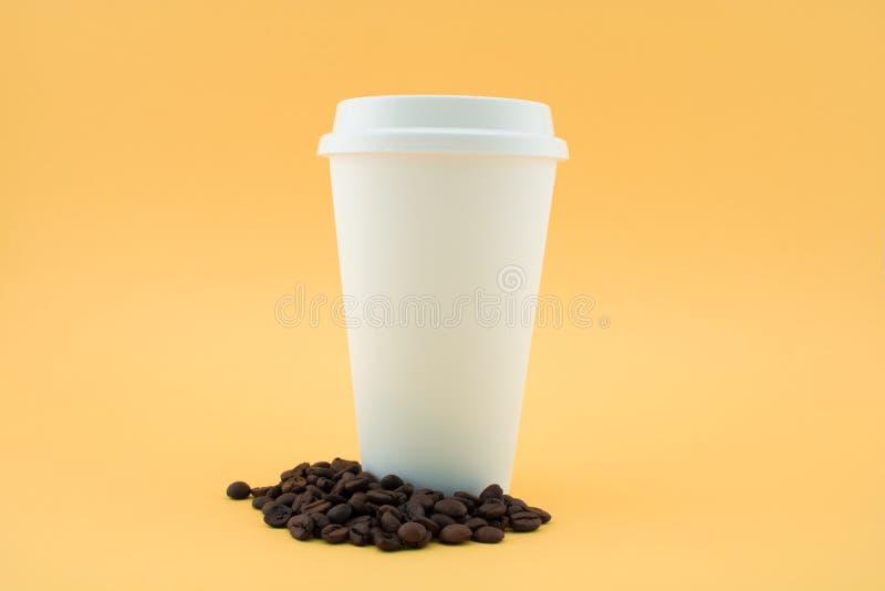 Tasse de café de papier sur des grains de café, fond jaune La tasse de café est couverte images stock