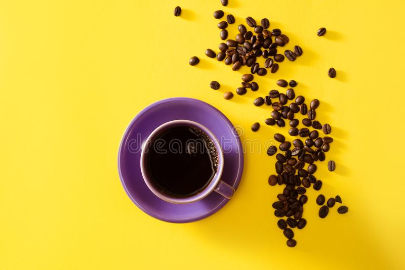 Tasse de café pourpre avec des grains de café sur le fond jaune image libre de droits
