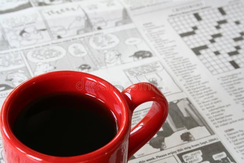 Tasse de café rouge avec le journal à l'arrière-plan photographie stock libre de droits