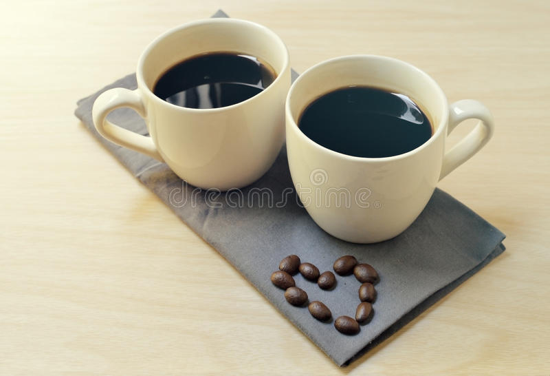 Tasse de café sur la table en bois avec la forme de coeur faite en haricot photo libre de droits