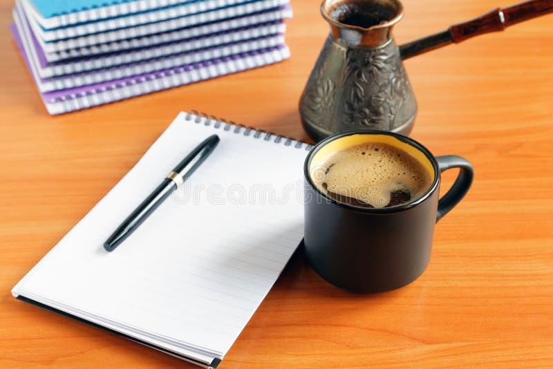 Tasse de café sur le bureau avec le carnet images libres de droits