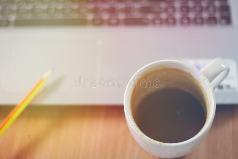 Tasse de café sur le bureau avec un ordinateur portable, un crayon, un dessus de table en bois avec la lumière du soleil lumineus image stock