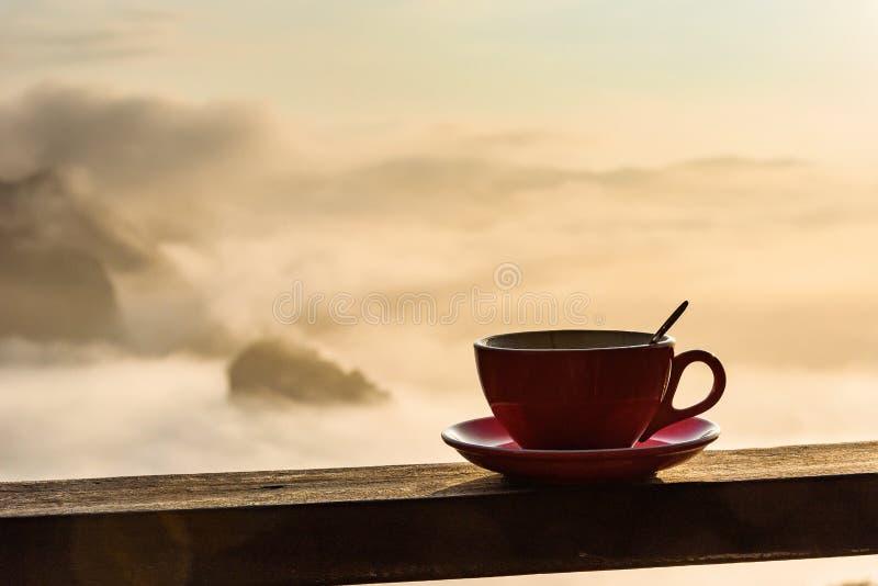 Tasse de café sur le plancher en bois avec le fond brumeux et de montagne T photos libres de droits