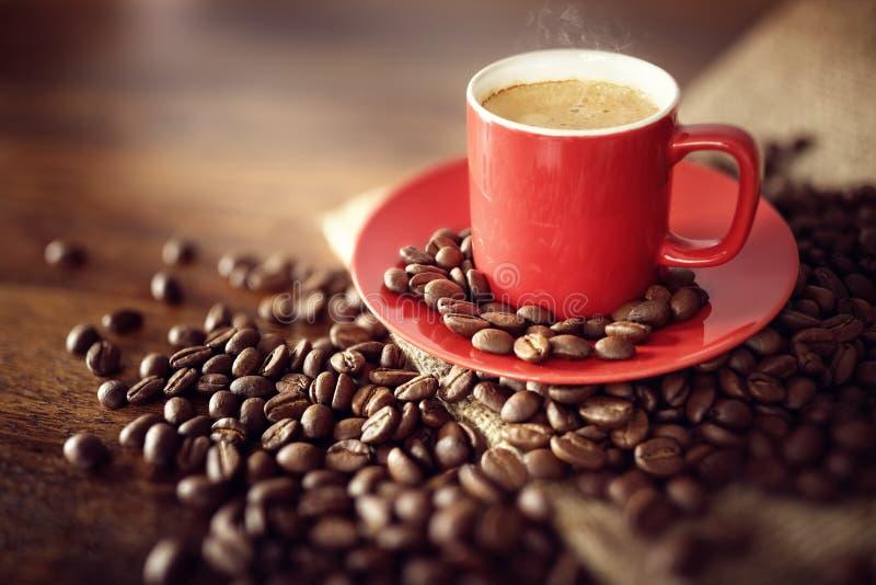Tasse de café sur le sac à toile de jute avec les haricots rôtis photographie stock