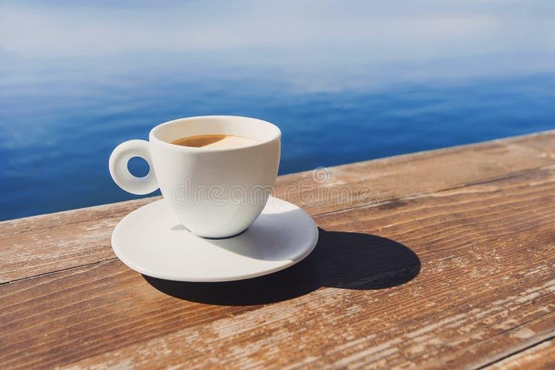 Tasse de café sur une table en bois au-dessus de fond de ciel bleu et de mer Concept de vacances d'?t? images libres de droits