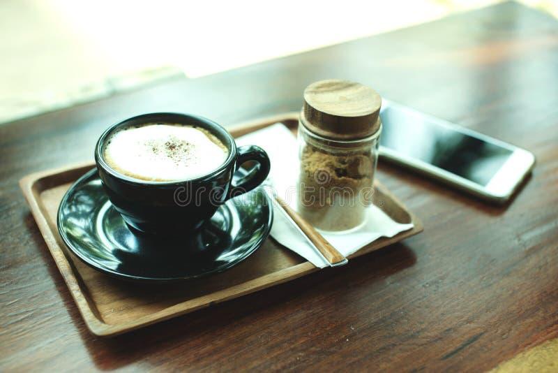 Tasse de café sur une table en bois avec le smartphone, l'espace de travail simple ou la pause-café avec surfer de Web images stock