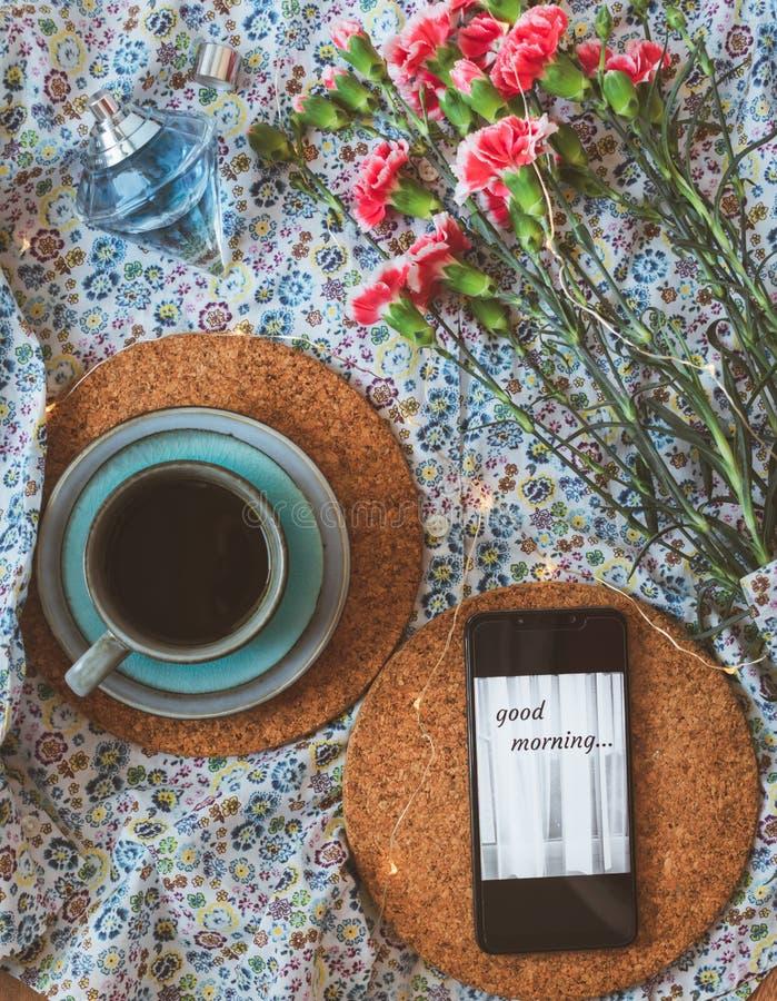 Tasse de café, de téléphone portable avec le message bonjour et d'oeillets roses sur le fond floral photo libre de droits