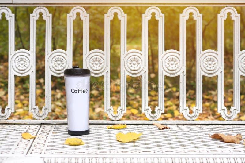 Tasse de café de voyage sur le banc dans le banc de parc d'automne images libres de droits