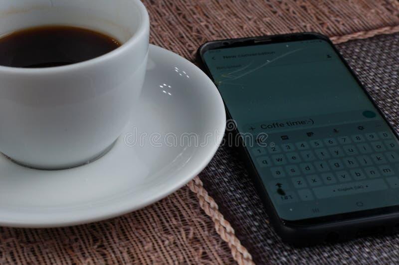 Tasse de caf? blanc avec le t?l?phone portable sur la table Temps de caf? images libres de droits