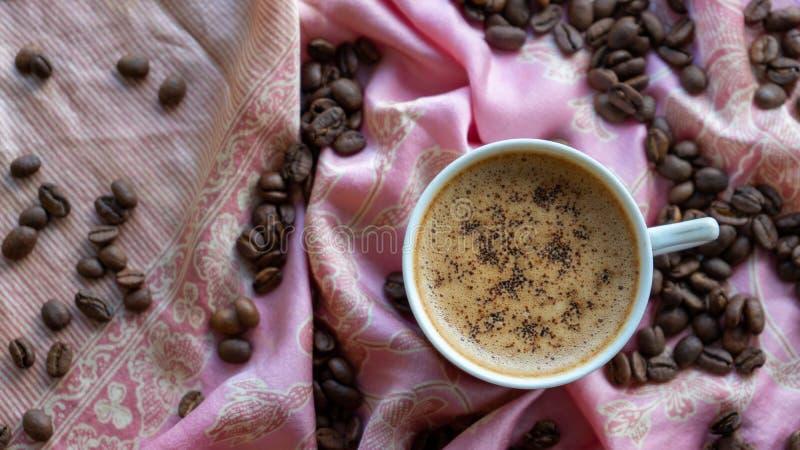 Tasse de caf? blanc et grains de caf? autour de elle avec le fond traditionnel de tissu illustration libre de droits
