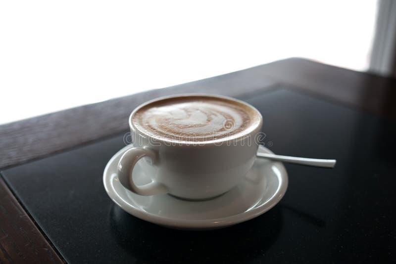 Tasse de cappuccino avec l'art de latte sur le fond noir de table Belle mousse, endroit pour le texte photos stock