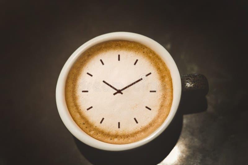 Tasse de cappuccino avec la position de visage d'horloge sur la fin noire de table  photos libres de droits