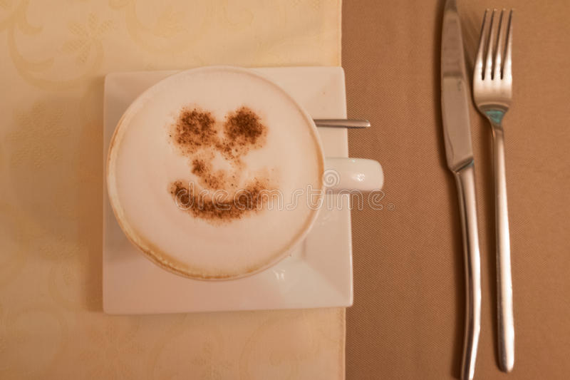 Tasse de cappuccino avec un sourire de cannelle sur une soucoupe blanche et des nappes beiges image stock
