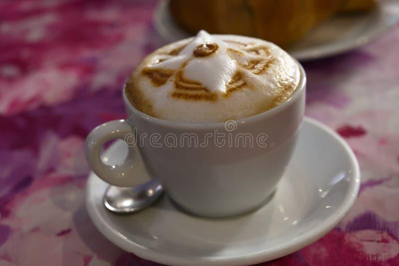 Tasse de cappuccino italien d'isolement sur la table rose photographie stock