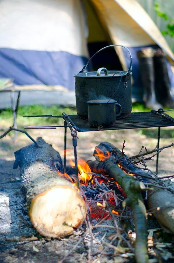 Tasse de chaudière et passionné de touristes au-dessus d'un feu de bois photos stock