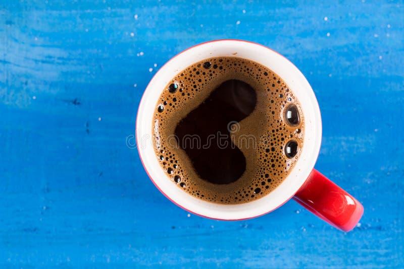 Tasse de configuration de café plate avec la forme de coeur au-dessus du fond en bois bleu image libre de droits