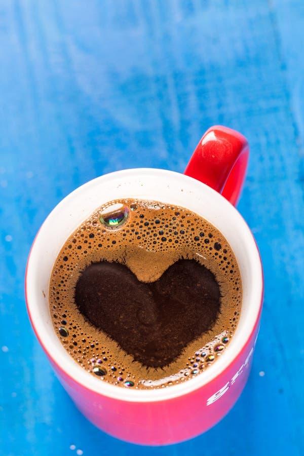 Tasse de configuration de café plate avec la forme de coeur au-dessus du fond en bois bleu photographie stock