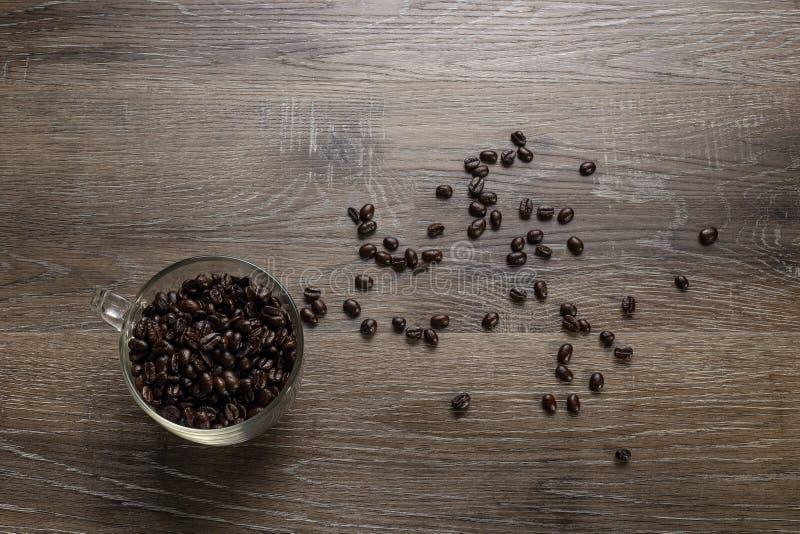 Tasse de grains de café sur un Tableau en bois image stock