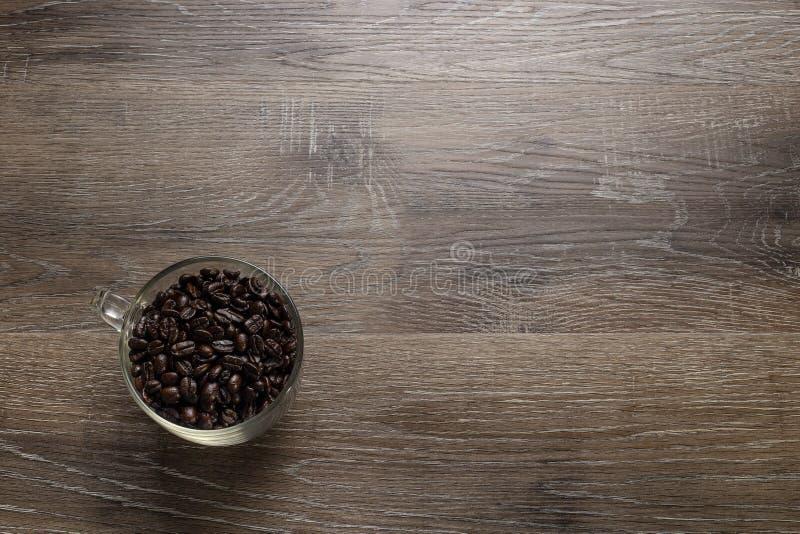 Tasse de grains de café sur un Tableau en bois image libre de droits