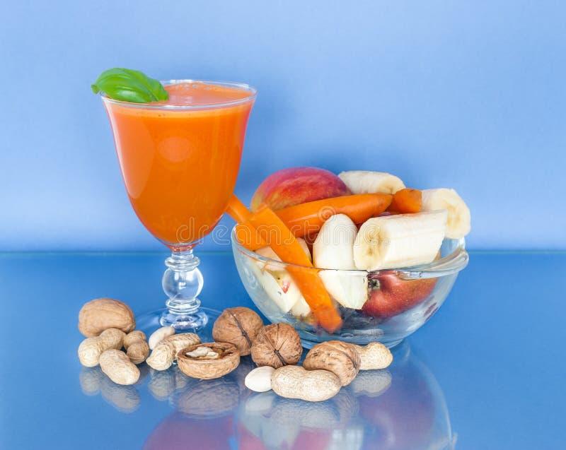 Tasse de jus de carotte avec des fruits frais dans un bol en verre et de divers écrous dispersés photos stock