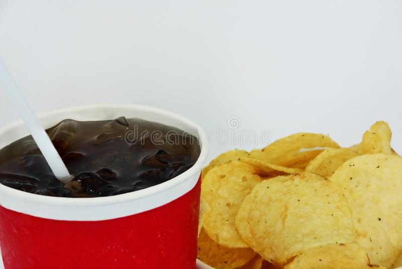 Tasse de kola avec des pommes chips sur le fond blanc image stock