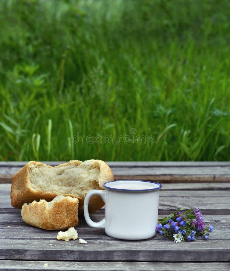 Tasse de lait avec le groupe de pain et de fleur images stock