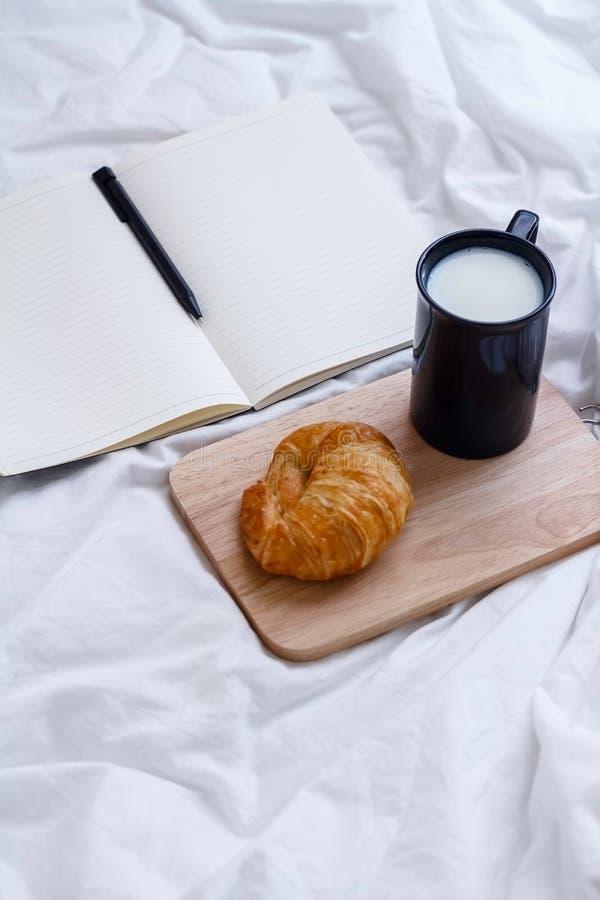tasse de lait, de croissant et de livre chauds sur la table de fonctionnement pendant le matin photos libres de droits