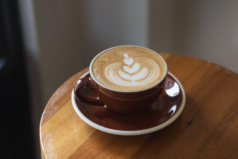 Tasse de latte chaud de café avec le beau style sur la table en bois à dedans photos stock
