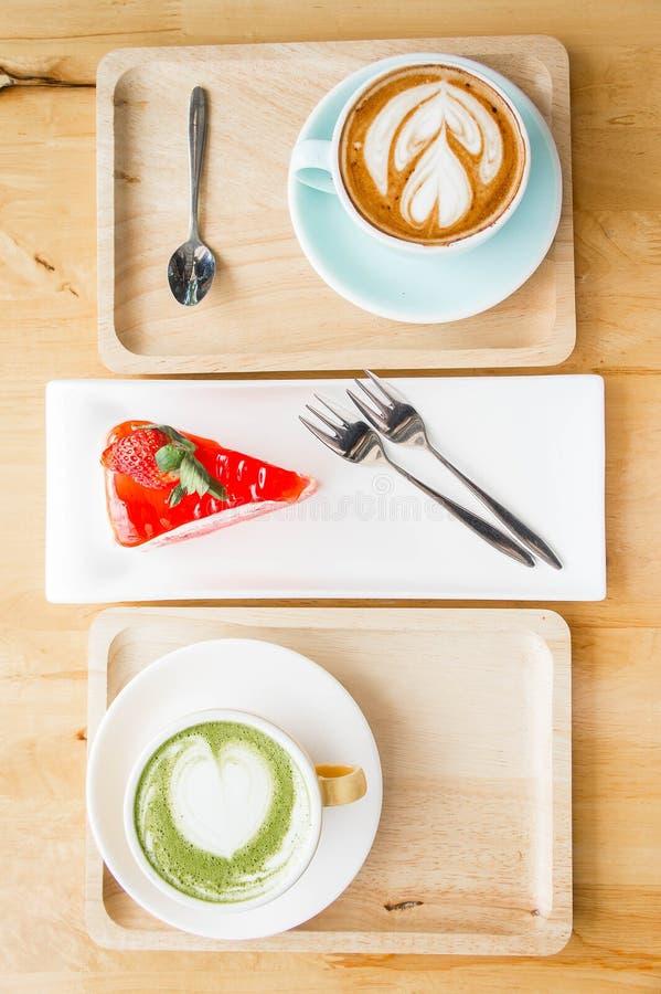 Tasse de latte de lait de thé vert sur la table en bois dans le café photographie stock
