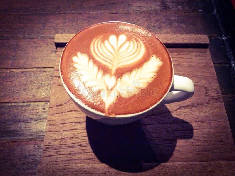 Tasse de latte ou de cappuccino chaud avec l'art fascinant de latte photo stock
