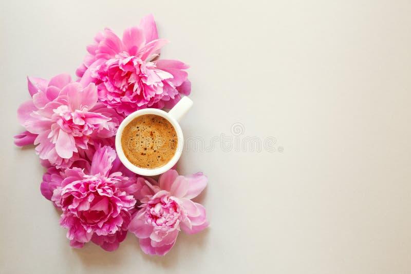 Tasse de matin de café et de belles fleurs fraîches de pivoine de rose de ressort sur le fond clair, vue supérieure, disposition  photographie stock