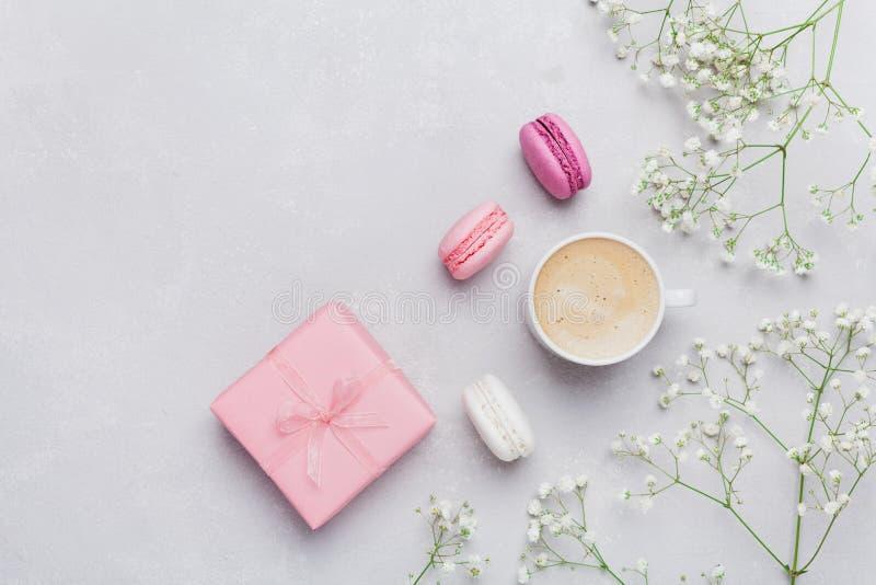 Tasse de matin de café, macaron de gâteau, cadeau ou boîte et fleur actuelles sur la table légère d'en haut Belle configuration d photographie stock libre de droits