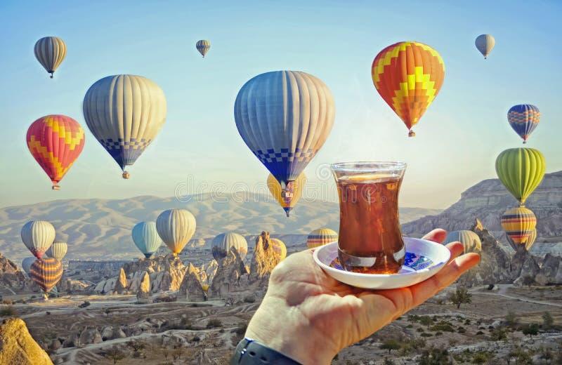 Tasse de matin de thé avec la vue des ballons à air chauds colorés photos stock